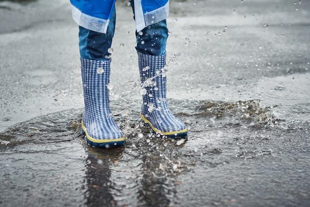 Ребенок в синих резиновых сапогах, перепрыгивая через лужу под дождем