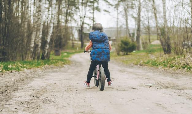 파란 조끼와 검은색 레깅스를 입은 아이가 시골의 흙길에서 균형 자전거를 탄다