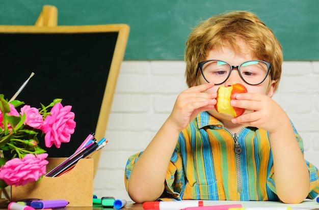 교실에서 아이입니다. 학교 급식. 사과를 먹는 귀여운 아이. 직장에서 초등학교에서 소년입니다.