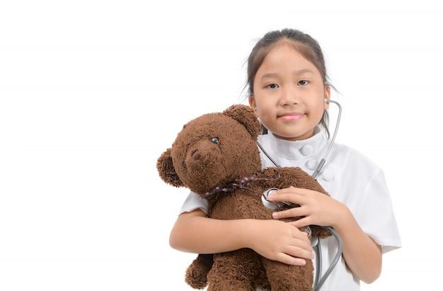 Ребенок в халате с помощью стетоскопа исследует плюшевого мишку