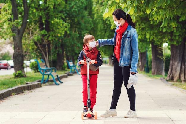 Ребенок в маске езда на скутере на улице. мальчик носит медицинскую маску. семья в масках безопасности на открытом воздухе.