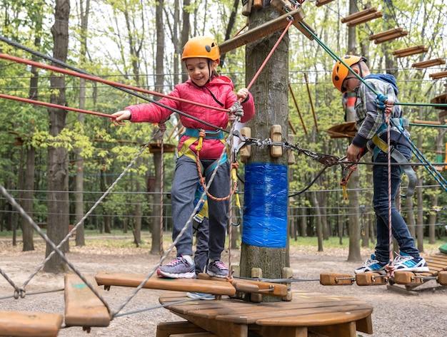森の冒険公園の子供。ロープウェイのある遊び場で屋外で遊ぶ子供たち。