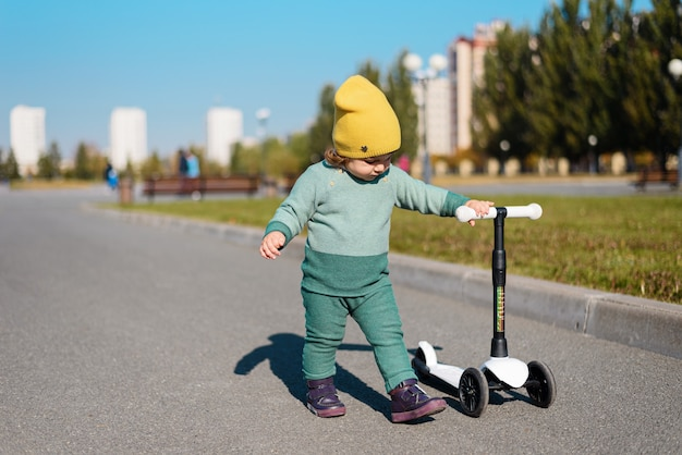 緑のスーツを着た子供、黄色い帽子が公園でスクーターに乗る、新鮮な空気の中でアクティブな遊び