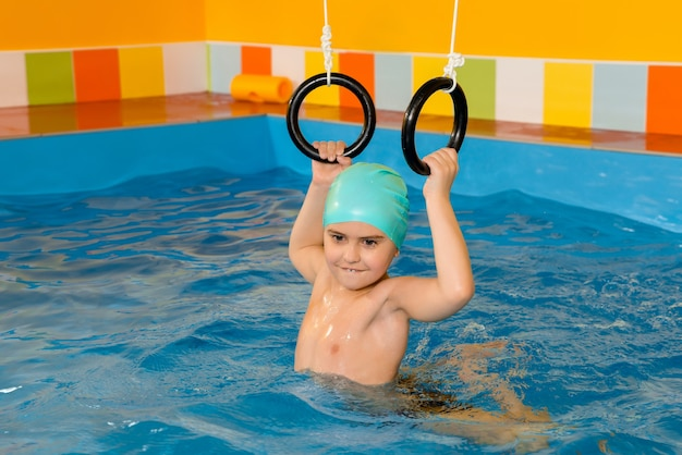 Ребенок в бассейне, тренируясь со спортивными кольцами