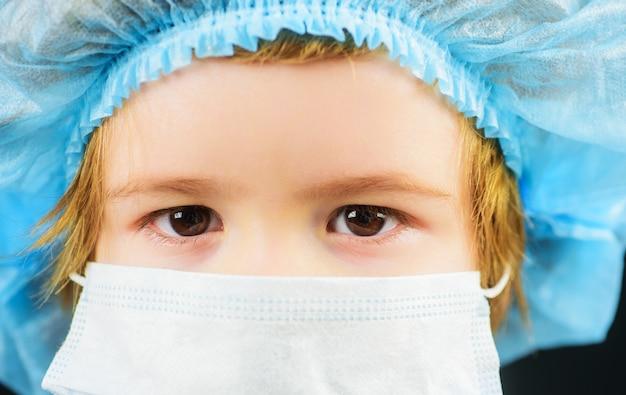 코비드-19 코로나바이러스 전염병으로부터 보호하기 위해 마스크를 쓴 아이. 질병 예방. 의료 모자와 마스크에 작은 소년. 확대.