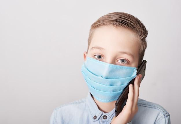 携帯電話で医療マスクの子。コロナウイルスと大気汚染pm2.5のコンセプト。ウイルス症状。流行、インフルエンザ、病気からの保護、ワクチン接種の概念。インフルエンザの病気。医療。