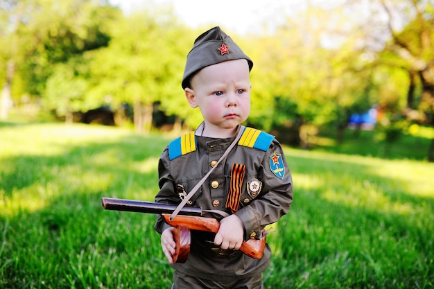 自然の背景に対して軍服の子供