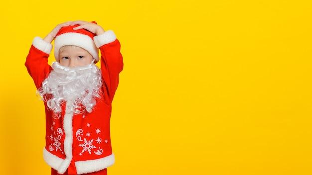 새해 산타클로스 의상을 입은 아이와 하얀 가짜 수염이 그의 머리 카피 공간을 움켜잡았다