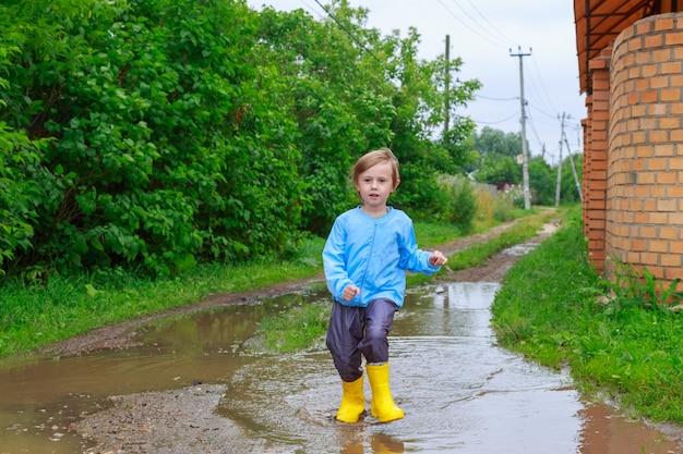 고무 장화와 웅덩이에서 달리는 비옷을 입은 어린이