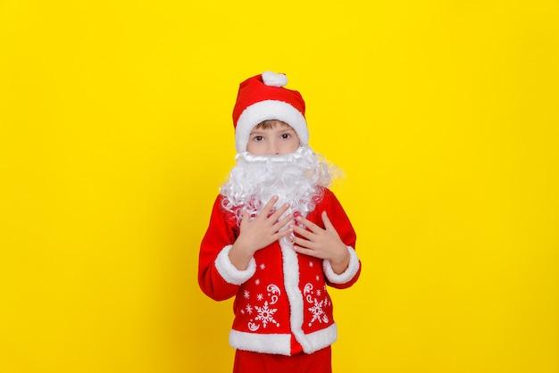 산타클로스 옷을 입은 아이와 가짜 수염이 스튜디오 노란색 배경에 서 있습니다.