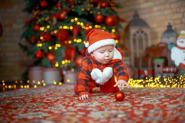 Ребенок в костюме санта-клауса возле новогодней елки в канун рождества с новым годом 2022 концепция