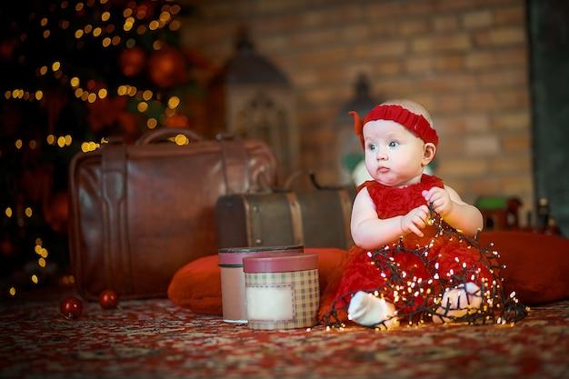 クリスマスイブの新年のツリーの近くにサンタクロースの衣装を着た子供幸せな新年2022年のコンセプト