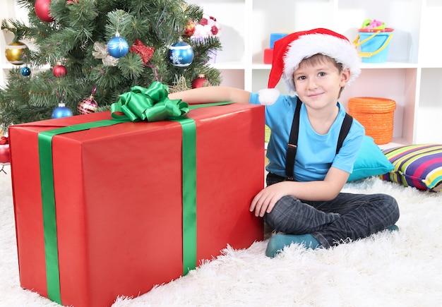 サンタの帽子をかぶった子供が手に大きな贈り物を持ってクリスマスツリーの近くに座っています