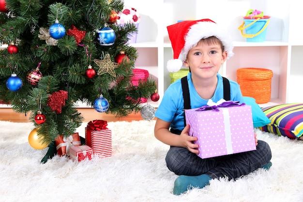 サンタの帽子をかぶった子供が手に贈り物を持ってクリスマスツリーの近くに座っています