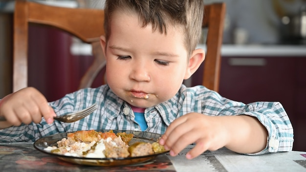 シャツを着た子供がクローズアップを食べています。