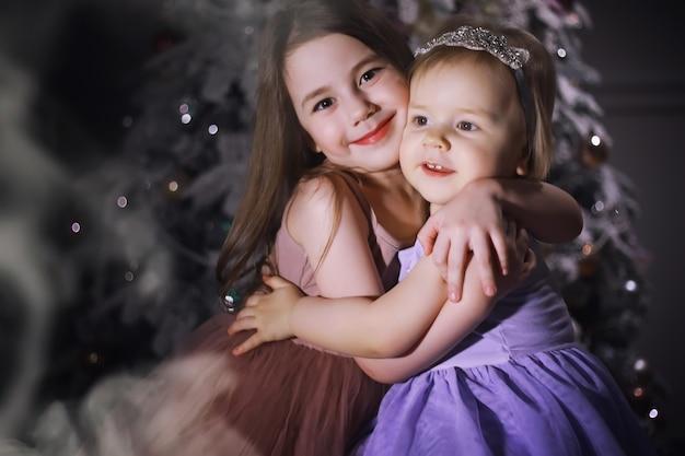 크리스마스 트리 앞에서 똑똑한 옷을 입은 아이. 새해 전날. 새해를 기다리고 있습니다.