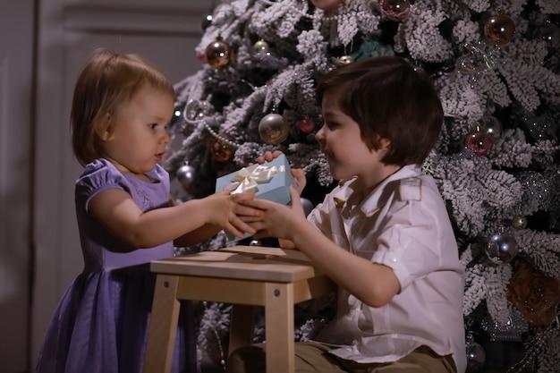 クリスマスツリーの前でスマートな服を着た子供。新年を待っています。