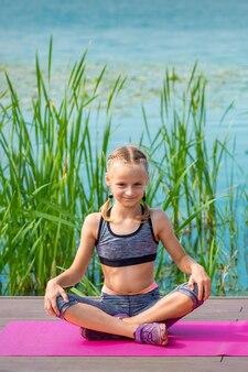 야외 물 근처 부두에 매트에 앉아 운동복에 아이