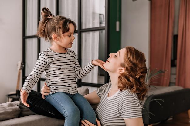 縞模様のtシャツを着た子供がソファに座って、母親の顔をなでています。