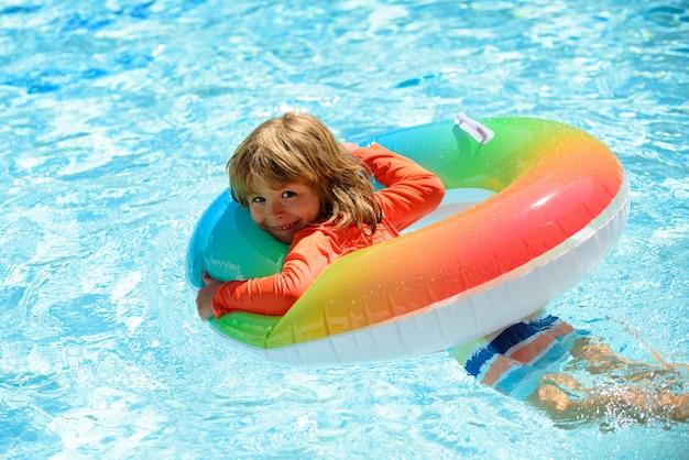 夏のプールの子供。夏の子供たちの休暇。夏の子供の週末。スイミングプールの少年。インフレータブルラバーサークルのアクアパークの少年。