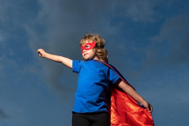 슈퍼맨 망토를 입은 아이. 슈퍼 히어로를 재생 하는 소년. 성공과 아이 승자 개념입니다.