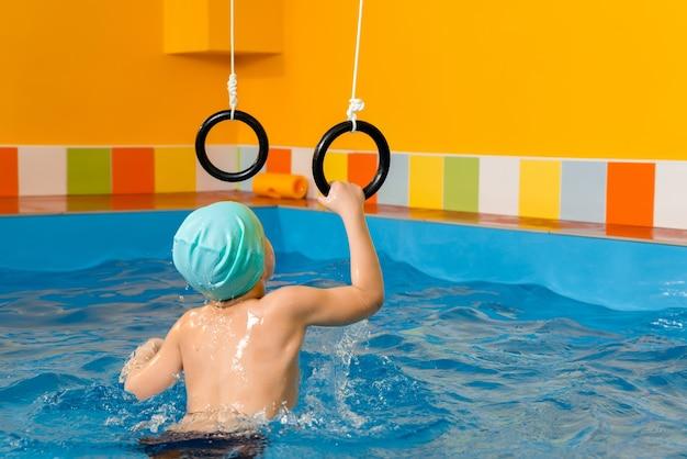 Ребенок в бассейне, упражнения со спортивными кольцами