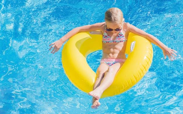 풍선 노란색 반지에 수영장에서 아이입니다.
