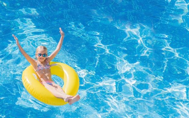 Ребенок в бассейне на надувном желтом кольце.