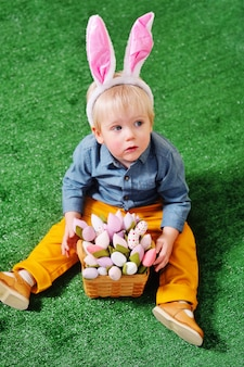 Ребенок в кусте зайчика с букетом цветов в корзине на траве. пасхальный заяц, 8 марта, весна, день матери