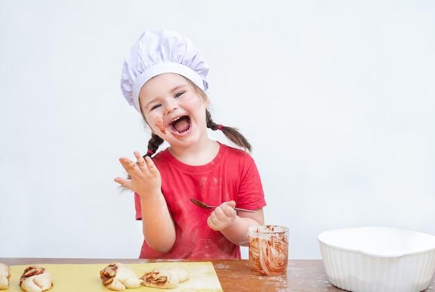 シェフの帽子をかぶった子供がベーキング用のフィリングを食べる