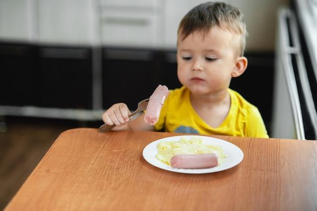 Ребенок на кухне ест колбасу и картофельное пюре