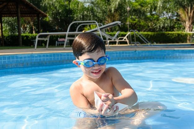 Ребенок в бассейне разрушает бумажный кораблик кулаком.