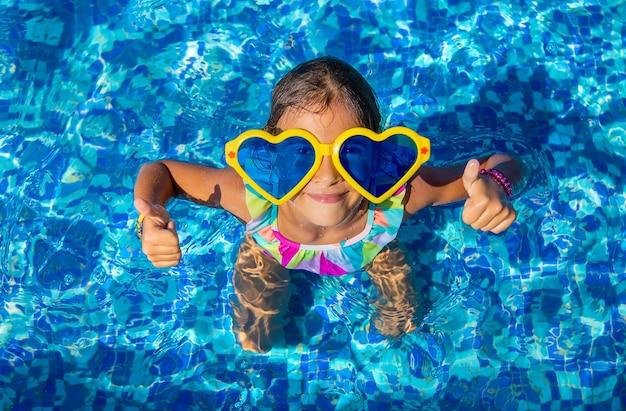 大きな眼鏡をかけているプールの子供。セレクティブフォーカス。子供。