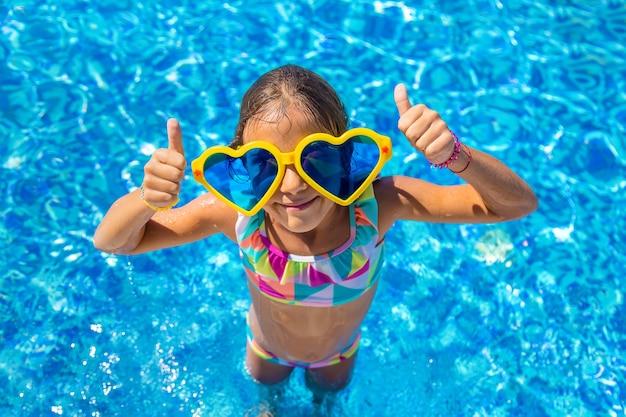 大きな眼鏡をかけているプールの子供。セレクティブフォーカス。