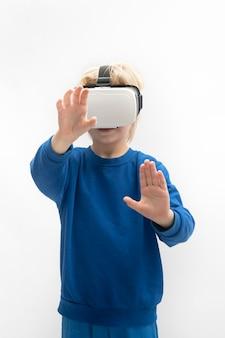 Ребенок в очках vr играет в игру виртуальной реальности. изолированный на белой поверхности. вертикальная рамка.