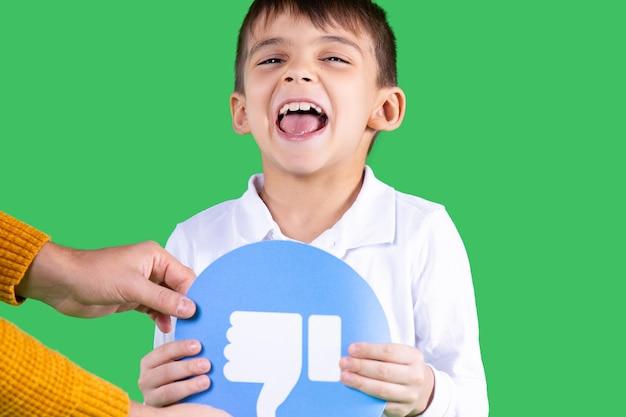 흰 셔츠를 입은 아이가 녹색 배경 아래로 엄지손가락을 아래로 내리며 종이 원 형태의 파란색을 팔에 안고 있습니다