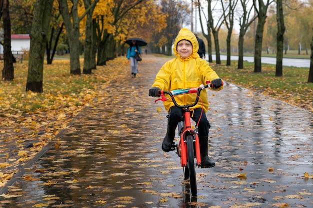 Ребенок в желтом плаще едет на велосипеде в осеннем парке. мальчик на велосипеде под дождем. портрет счастливого дошкольника.