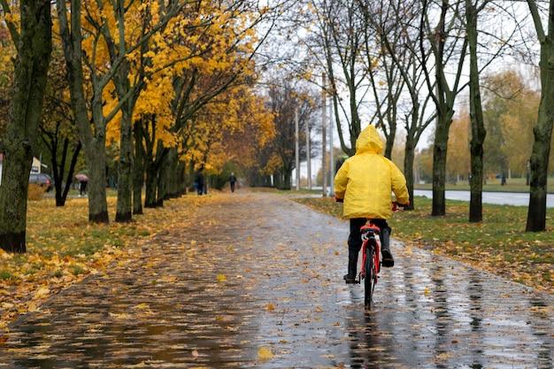 Ребенок в желтом плаще едет на велосипеде в осеннем парке во время дождя. вид сзади.