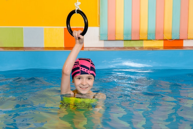 Child in inside swimming pool excersizing with sport rings