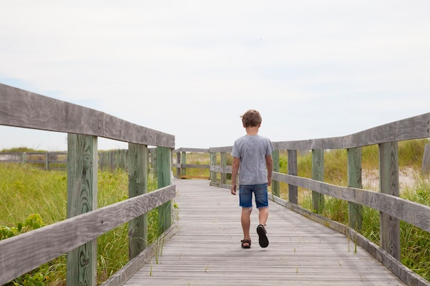 Ребенок один в дороге. мальчик теряется и идет вперед. мальчик хочет побыть один. вид сзади ребенка, демонстрирующего негодование и уходящего
