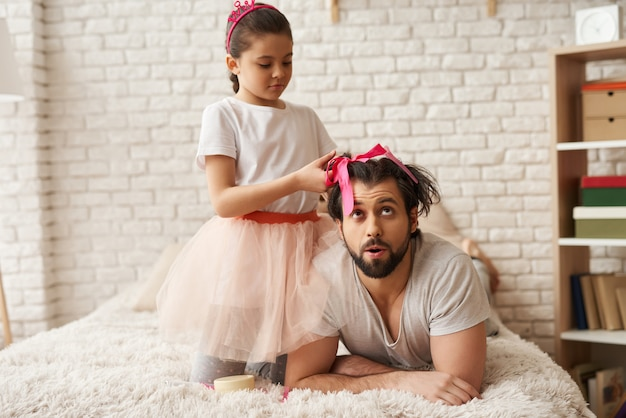 Child is braiding fathers hair