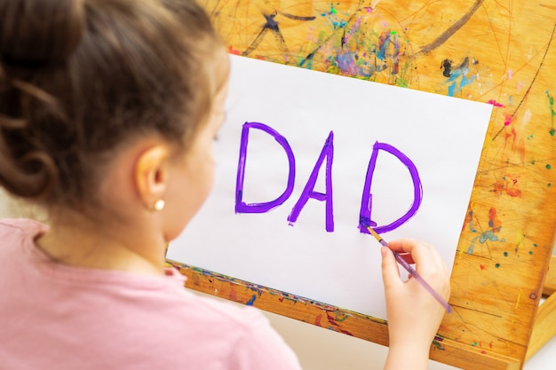 Child is drawing father's day greeting card