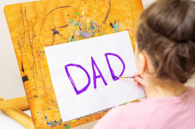 아이가 아버지의 날 인사말 카드를 그리고 있습니다.