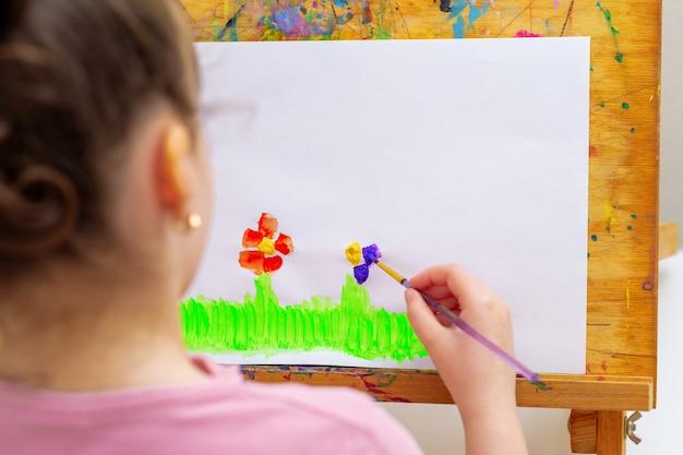 子供は花を描いています