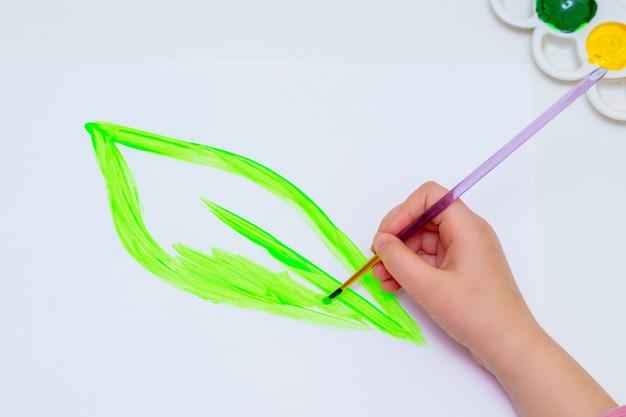 Ребенок рисует зеленый лист