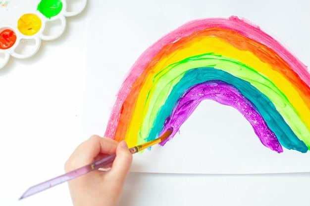 Ребенок рисует радугу.