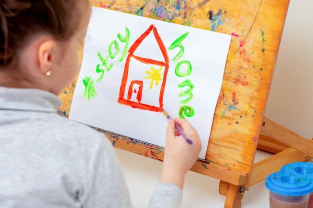 아이는 집에 있는 동안 쓰여진 문구와 함께 수채화로 빨간 집을 그리고 있다