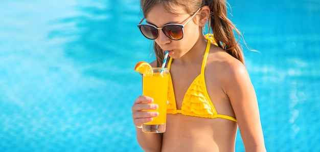 The child is drinking a cocktail by the pool