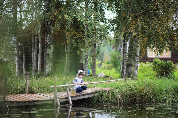 A child is fishing in the autumn morning. autumn sunset on the pond. a fisherman with a fishing rod on the walkway.