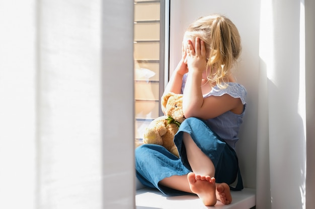 Child is a girl alone at home. girls sitting on the windowsill and crying looking out the window.